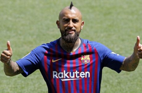 Barcelona's new signing Chilean soccer player Arturo Vidal gestures during his official presentation at the Camp Nou stadium in Barcelona, Spain, Monday, Aug. 6, 2018. (AP Photo/Manu Fernandez)