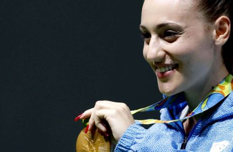 Anna Korakaki of Greece displays her gold medal following the victory ceremony for the women's 25-meter pistol event at the Olympic Shooting Center at the 2016 Summer Olympics in Rio de Janeiro, Brazil, Tuesday, Aug. 9, 2016. (AP Photo/Hassan Ammar)