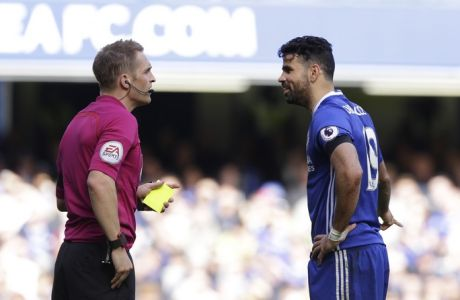 Referee Craig Pawson, left, shows a yellow card to Chelsea's Diego Costa for a foul during their English Premier League soccer match between Chelsea and Crystal Palace at Stamford Bridge stadium in London, Saturday, April 1, 2017. (AP Photo/Alastair Grant)