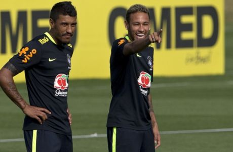 Brazil's Paulinho, left and Neymar, stand on the pitch during a training session in preparation for an upcoming World Cup qualifying match, in Teresopolis, Brazil, Monday, Oct. 2, 2017. (AP Photo/Silvia Izquierdo)