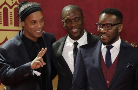 Brazilian soccer star and former FC Barcelona player Ronaldinho, left, former Dutch soccer player Clarence Seedorf, center, and former Nigerian soccer player Jay Jay Okocha arrive for the 2018 soccer World Cup draw in the Kremlin in Moscow, Friday, Dec. 1, 2017. (AP Photo/Dmitri Lovetsky)