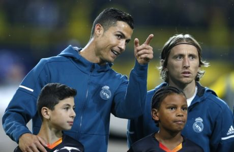 Real Madrid's Cristiano Ronaldo points as he lines up next to Real Madrid's Luka Modric prior to a Champions League Group H soccer match between Borussia Dortmund and Real Madrid at the BVB stadium in Dortmund, Germany, Tuesday, Sept. 26, 2017. (AP Photo/Michael Probst)