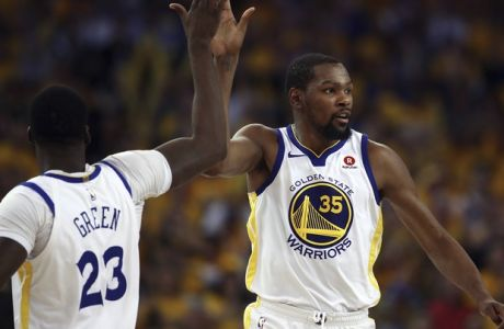 Golden State Warriors' Kevin Durant (35) celebrates a score with Draymond Green, left, as San Antonio Spurs' Rudy Gay (22) watches during the second half in Game 1 of a first-round NBA basketball playoff series Saturday, April 14, 2018, in Oakland, Calif. (AP Photo/Ben Margot)