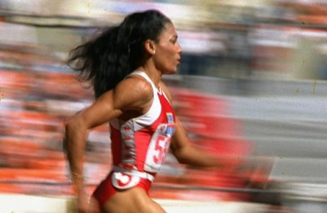 U.S. sprinter Florence Griffith Joyner of Los Angeles strides to a world record in a semifinal heat of the Olympic women's 200-meter dash in Seoul Thursday, Sept. 29, 1988.  Joyner's time of 21.56 seconds claimed the record and moved her into the finals in the event.(AP Photo/Lennox McLendon)