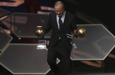 Real Madrid's President Florentino Perez carries his two trophies after he was selected for the Best President and the Best Club of the Year, during the Dubai Football Gala & Globe Soccer Awards Ceremony in Dubai, United Arab Emirates, Tuesday, Dec. 27, 2016. (AP Photo/Kamran Jebreili)