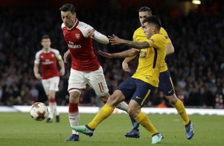 Arsenal's Mesut Ozil, left, keeps the ball as Atletico's players try to stop him during the Europa League semifinal first leg soccer match between Arsenal FC and Atletico Madrid at Emirates Stadium in London, Thursday, April 26, 2018. (AP Photo/Matt Dunham)