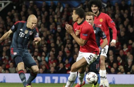 Bayern's Arjen Robben, left, shoots past Manchester United's Rio Ferdinand during the Champions League quarterfinal first leg soccer match between Manchester United and Bayern Munich at Old Trafford Stadium, Manchester, England, Tuesday, April 1, 2014.(AP Photo/Jon Super)