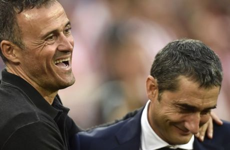 FC Barcelona's head manager Luis Enrique, left, smiles beside Athletic Bilbao's head manager Ernesto Valverde during their Spanish La Liga soccer match between FC Barcelona and Athletic Bilbao, at San Mames stadium, in Bilbao, northern Spain, Sunday, Aug. 28, 2016. FC Barcelona won the match 1-0. (AP Photo/Alvaro Barrientos)