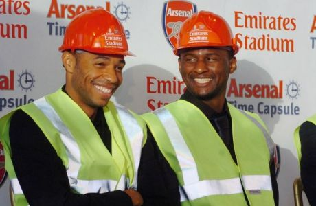 Arsenal manager Arsene Wenger, right, and players Thierry Henry, left, and Patrick Vieira share a joke before placing a specially-made time capsule containing memories and keepsakes from Arsenal's present stadium, Highbury, underneath their new Emirates Stadium in north London, Thursday Oct. 28, 2004. The time capsule, which will be on view to supporters when the Emirates Stadium opens in August 2006, contains nearly 40 items including a replica home shirt from the 1913/14 season and a replica model of Highbury. (AP Photo/Johnny Green, Pool)