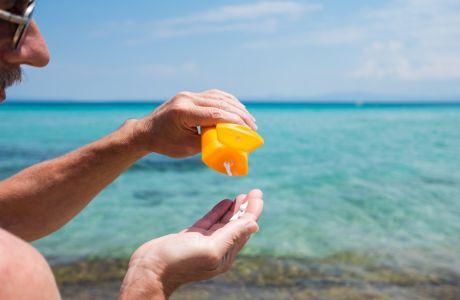 Senior man using sun protection cream on summer vacation