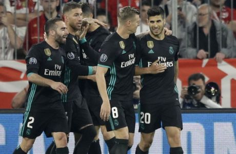 Real Madrid's Marco Asensio, right, is congratulated by his teammates after scoring their second goal during the semifinal first leg soccer match between FC Bayern Munich and Real Madrid at the Allianz Arena stadium in Munich, Germany, Wednesday, April 25, 2018. (AP Photo/Matthias Schrader)