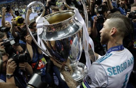 Real Madrid's Sergio Ramos celebrates with the trophy after winning the Champions League Final soccer match between Real Madrid and Liverpool at the Olimpiyskiy Stadium in Kiev, Ukraine, Saturday, May 26, 2018. (AP Photo/Matthias Schrader)