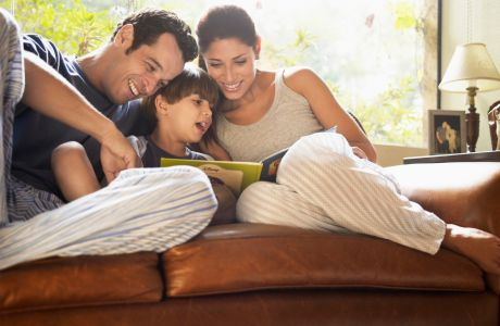 Parents and son reading book on sofa