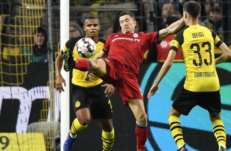Bayern's Robert Lewandowski, center, Dortmund's Manuel Akanji, left, and Dortmund's Julian Weigl challenge for the ball during the German Bundesliga soccer match between Borussia Dortmund and FC Bayern Munich in Dortmund, Germany, Saturday, Nov. 10, 2018. (AP Photo/Martin Meissner)