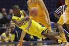Michigan's Caris LeVert falls as he tries to pass around Tennessee's Darius Thompson during the second half of an NCAA Midwest Regional semifinal college basketball tournament game Friday, March 28, 2014, in Indianapolis. (AP Photo/David J. Phillip)