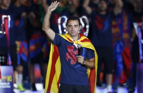 Barcelona's Xavi Hernandez waves to the fans during celebrations at the Camp Nou stadium in Barcelona, Spain Sunday June 7, 2015 after winning the Champions League final soccer match Saturday by beating Juventus Turin 3-1. Barcelona won the triple this season winning the Spanish League title, the Copa del Rey and the Champions League. (AP Photo/Manu Fernandez)