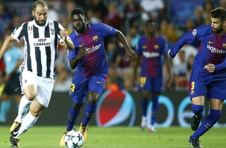 Juventus' Gonzalo Higuain fights for the ball against Barcelona's Samuel Umtiti during a group D Champions League soccer match between FC Barcelona and Juventus at the Camp Nou stadium in Barcelona, Spain, Tuesday, Sept. 12, 2017. (AP Photo/Manu Fernandez)