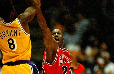 Chicago Bulls Michael Jordan (23) reaches to defend against Los Angeles Lakers Kobe Bryant (8) during the second quarter action, Feb. 1, 1998 in Inglewood, California. Lakers routed the Bulls, 112-87. (AP Photo/Kevork Djansezian)