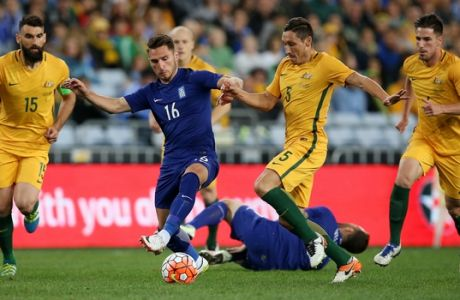 Greece's Dimitrios Diamantakos, center left, and Australia's Mark Milligan, center right, compete for the ball during their soccer friendly in Sydney, Saturday, June 4, 2016. (AP Photo/Rick Rycroft)