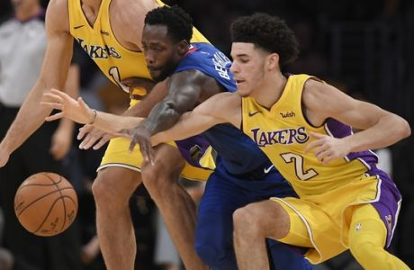 Los Angeles Lakers center Brook Lopez, left, and guard Lonzo Ball, right, reach for a loose ball along with Los Angeles Clippers guard Patrick Beverley during the first half of an NBA basketball game, Thursday, Oct. 19, 2017, in Los Angeles. (AP Photo/Mark J. Terrill)