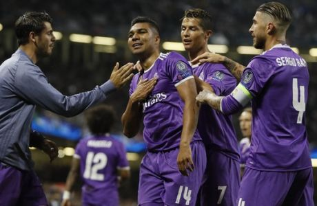 Real Madrid's Casemiro, left, celebrate with his teammates Cristiano Ronaldo, center and Sergio Ramos during the Champions League final soccer match between Juventus and Real Madrid at the Millennium Stadium in Cardiff, Wales, Saturday June 3, 2017. (AP Photo/Kirsty Wigglesworth)