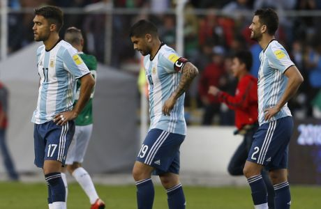 Argentina's Matias Caruzzo, left, Ever Vanegas, center, and Mateo Musacchio leave the field at the end of a 2018 Russia World Cup qualifying soccer match against Bolivia, at the Hernando Siles stadium in La Paz, Bolivia, Tuesday, March 28, 2017. Bolivia won 2-0. (AP Photo/Juan Karita)