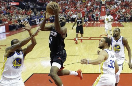 Houston Rockets guard James Harden (13) drives to the basket past Golden State Warriors defenders Andre Iguodala (9), Stephen Curry (30), and Kevin Durant (35) during the first half in Game 2 of the NBA basketball Western Conference Finals, Wednesday, May 16, 2018, in Houston. (AP Photo/David J. Phillip)