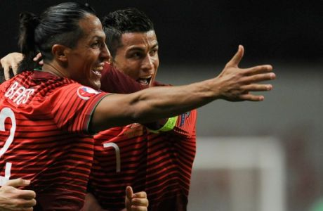 Portugals Cristiano Ronaldo, right, and Bruno Alves celebrate after Joao Moutinho scored the opening goal during the Euro 2016 qualifying group I soccer match between Portugal and Denmark at the Municipal Stadium in Braga, Portugal, Thursday, Oct. 8 2015. (AP Photo/Paulo Duarte)