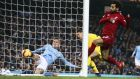 Manchester City's John Stones, left, clears the ball off the line during the English Premier League soccer match between Manchester City and Liverpool at the Etihad Stadium in Manchester, England, Thursday, Jan. 3, 2019. (AP Photo/Dave Thompson)