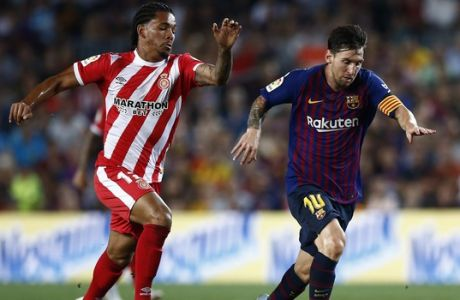 FC Barcelona's Lionel Messi, left, duels for the ball against Girona's Douglas Luiz during the Spanish La Liga soccer match between FC Barcelona and Girona at the Camp Nou stadium in Barcelona, Spain, Sunday, Sept. 23, 2018. (AP Photo/Manu Fernandez)