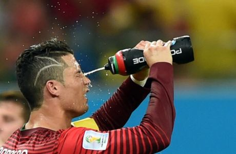 TOPSHOTS  Portugal's forward Cristiano Ronaldo cools himself during a break in the first half in a Group G match between USA and Portugal at the Amazonia Arena in Manaus during the 2014 FIFA World Cup on June 22, 2014.  AFP PHOTO / FRANCISCO LEONGFRANCISCO LEONG/AFP/Getty Images