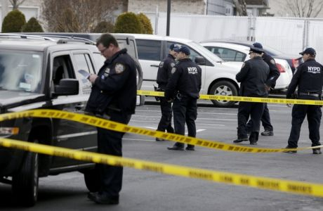 FILE - In a Wednesday, Feb. 10, 2016 file photo, police officers stand in the parking lot of a Ramada Inn, where authorities say a man stabbed a woman and her children in the Staten Island borough of New York. Police on Saturday, Feb. 13 arrested fugitive Michael Sykes, suspected of the stabbings, in Queens, ending a four-day manhunt. Sykes was brought back to a police precinct on Staten Island, where he was arrested on three counts of murder, attempted murder and robbery charges.  (AP Photo/Seth Wenig)