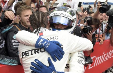 Mercedes driver Lewis Hamilton of Britain, front left, celebrates with second placed Mercedes driver Valtteri Bottas of Finland after winning the German Formula One Grand Prix at the Hockenheimring racetrack in Hockenheim, Germany, Sunday, July 22, 2018. (AP Photo/Jens Meyer)