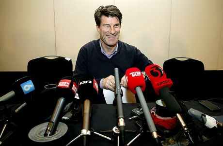 Danish soccer coach Michael Laudrup smiles to members of the media following a news conference in  London, Tuesday, Feb. 18, 2014. Laudrup says he is considering taking legal action after being sacked as manager of Swansea City. The Dane, who led the Swans to League Cup success last year, added he had not been allowed to return to the training ground to say goodbye to staff. In a statement issued by the League Managers' Association (LMA), he claimed he is still waiting to hear the reasons why he was dismissed. 'I am, of course, taking legal advice,' he said. (AP Photo/Lefteris Pitarakis)